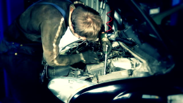 car mechanics with a spanner checking engine under hood in car service station video