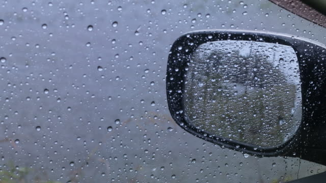 Car mirror with rain drops. The view from the inside of the car through the side mirrors, which are droplets of thunderstorms in the countryside. ominous stock videos & royalty-free footage