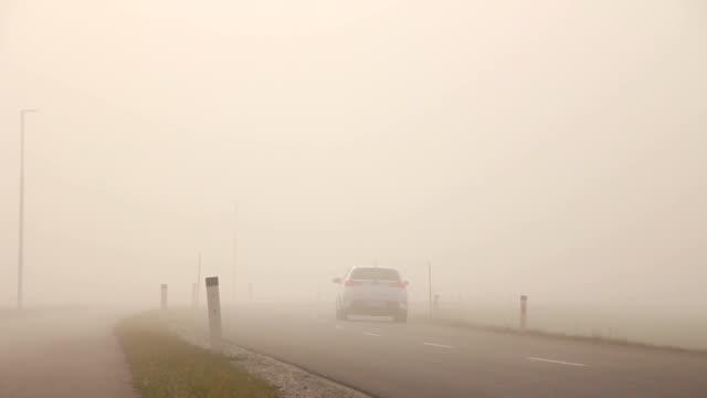 Car on a empty foggy road video