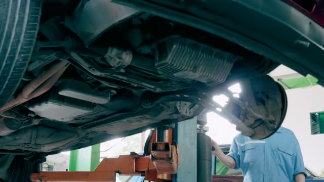 Car on car jack in auto repair shop, taking it down slowly. video