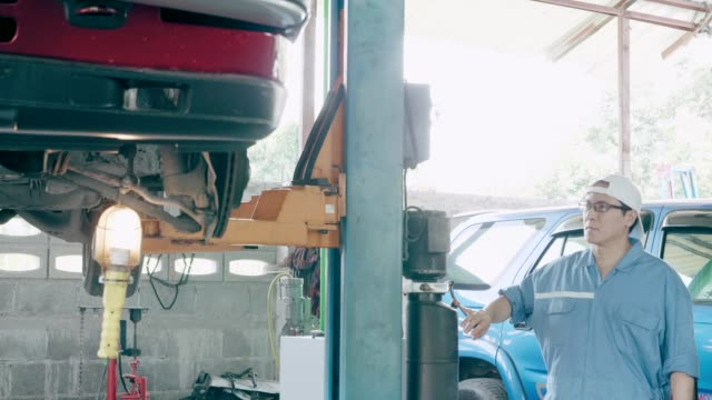 Car on car jack in auto repair shop, taking it down slowly.