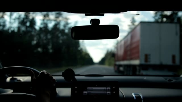 Car overtaking big truck on highway Car overtaking truck on motorway in the forest. View from inside of vehicle's interior. Woman driving car on high speed motorway and overtaking lorry during summer road trip. dashboard vehicle part stock videos & royalty-free footage