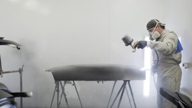 Car painter spraying black paint on hood