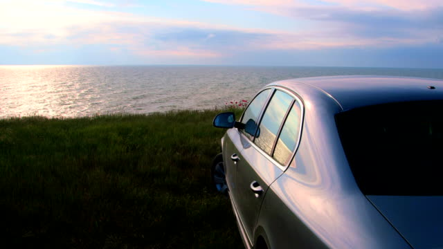 Car parked on the seashore at sunset video