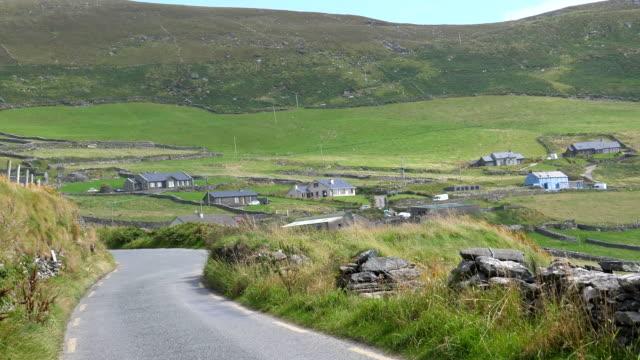 stockvideo's en b-roll-footage met de mening die van de autopassagier door dorp dunquin in ierland drijft - dorp