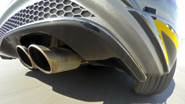 Car racing at a sports track Competitive sports car driving at a sports track on a sunny day, view of exhaust pipe. Shot in real time sports car stock videos & royalty-free footage