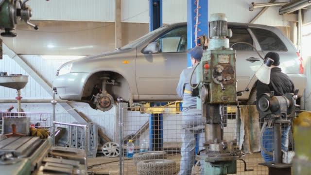 車の修理工場、車のリフト。 - 機械工点の映像素材/bロール
