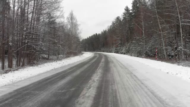 Car rushes along a snow-covered road in the woods. Dangerous driving in icy conditions