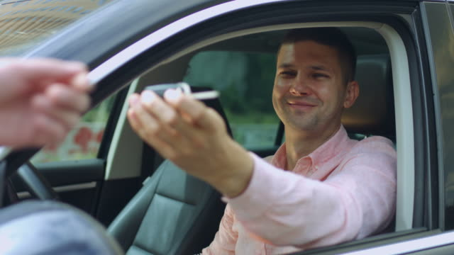 Car salesman giving the key to the new car owner Portrait of excited handsome man buying new car in dealership and receiving keys from manager. Happy male driver receiving car keys of his new vihicle and smiling while sitting inside of automobile. car key stock videos & royalty-free footage