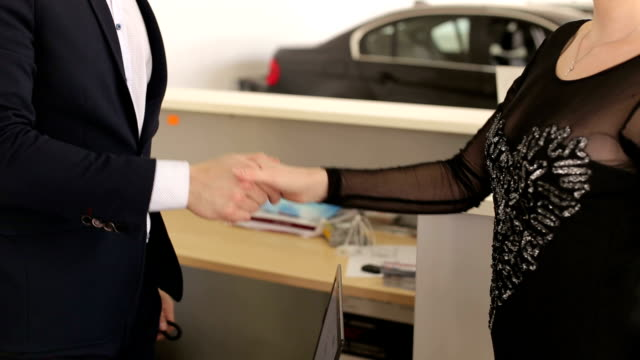 Car salesman shakes hands with a young girl and gives the keys to the new car.
