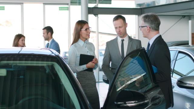otomobil satıcıları araba bayiliğinde iş stratejisini tartışıyor - i̇yi giyimli stok videoları ve detay görüntü çekimi