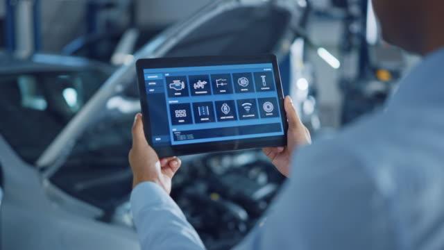 car service manager eller mechanic använder en tablet dator med en futuristisk interaktiv diagnostik programvara. specialist som inspekterar fordonet för att hitta trasiga komponenter i motorrummet. - maskindel bildbanksvideor och videomaterial från bakom kulisserna