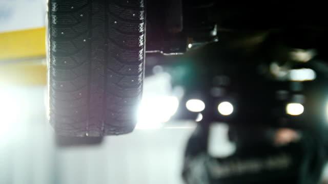 自動車サービス - メカニック リフト車の下で仕事をしながら自動車デバイスを外してホイールします。 ビデオ