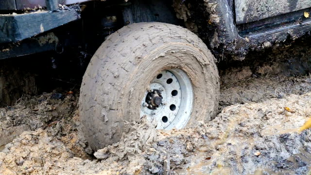 SUV 4WD car stuck in muddy off-road SUV 4WD car stuck in muddy off-road. Closeup the wheel rotates in the mud. mud stock videos & royalty-free footage