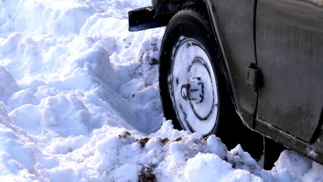 vídeos y material grabado en eventos de stock de un auto atascado en la nieve convierte las ruedas - nieve amontonada