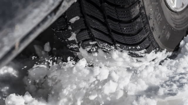 Car stuck in winter, spraying snow over camera