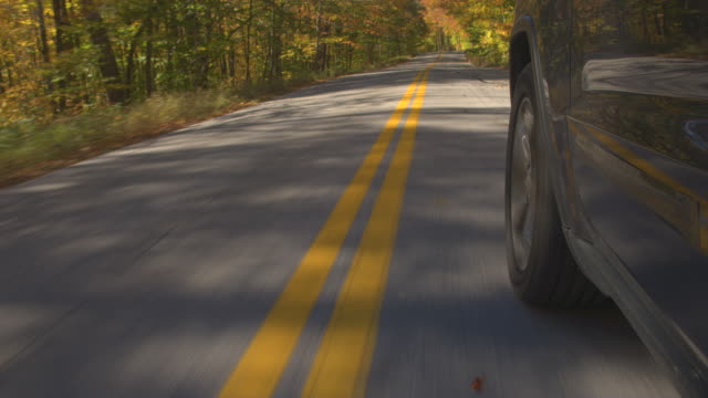 CLOSE UP: Car tire driving along double yellow lines on autumn forest road