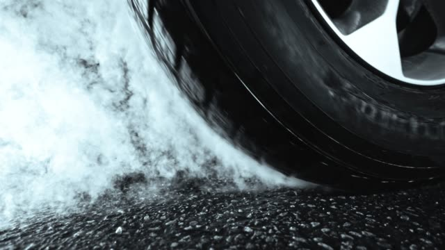 SLO MO Car tire heating up and smoking Slow motion medium locked down shot of a car tire heating up and causing smoke during a burnout. Shot in Slovenia. tires stock videos & royalty-free footage
