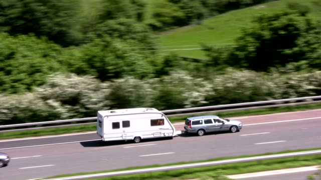 Car towing caravan and white van on motorway a silver mid size saloon car towing a white caravan, followed by a small white van, both travelleing on the M6 motorway sweeping through the eastern edge of the Lake District fells. towing stock videos & royalty-free footage