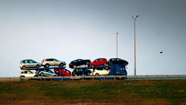 Car trailer on a highway. Closeup side view panning shot of a truck pulling a car trailer loaded with cars of different brands and moving on a highway. car dealership stock videos & royalty-free footage