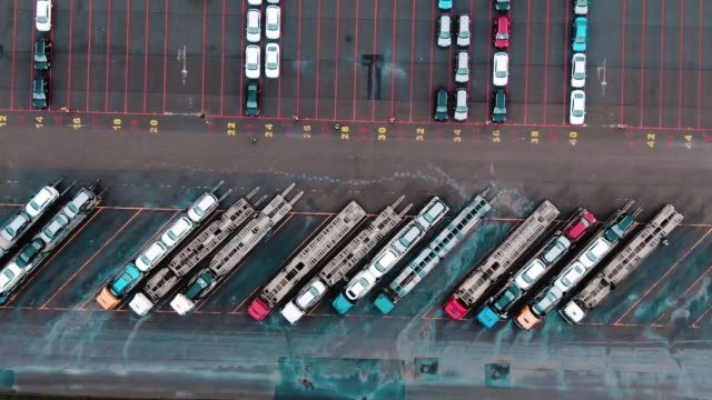 car transporter trucks stand on huge parking lot aerial view loaded and unloaded car transporter trucks stand in rows on huge factory warehouse parking for finished cars aerial view car transporter stock videos & royalty-free footage