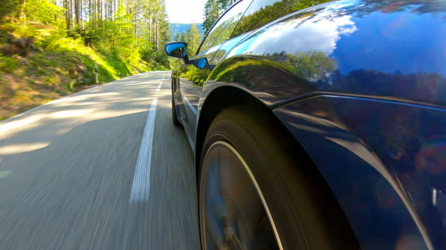 car travel on an empty scenic winding road, side view - strada tortuosa video stock e b–roll