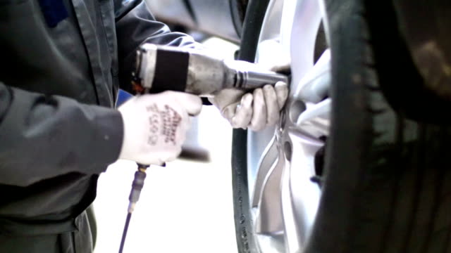 Car tyre replacement. Closeup of unrecognizable male mechanic replacing car tire at a workshop.  He's using pneumatic torque screwdriver to loosen the bolts holding the wheel. The car is lifted up on a jack.The mechanic is wearing working uniform and white protective gloves.Side view. vehicle part stock videos & royalty-free footage