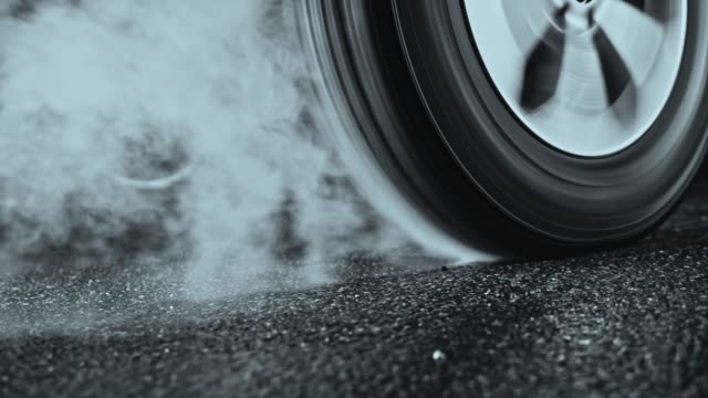 Car tyre rotating in place and smoking Wide handheld shot of a car tyre smoking while being rotated in place. Shot in Slovenia. tires stock videos & royalty-free footage