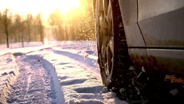 SLO MO Car tyre splashing snow into the camera