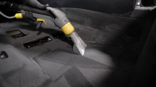 car washer is using vacuum cleaner over carpet inside a car during professional washing in auto-service - moquette video stock e b–roll