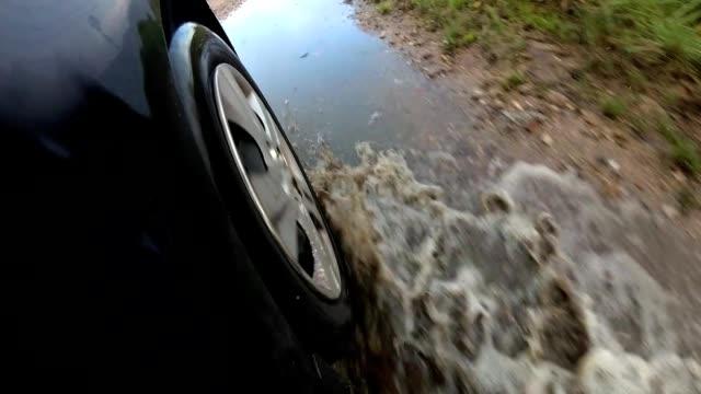 Car Wheel Driving Through Deep Puddle Slow Motion POV video