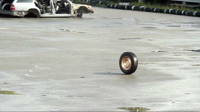 Car wheel rolling on asphalt after accident, crash. Junkyard video