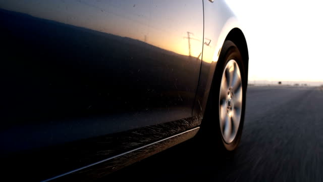 Car wheel spinning POV - Close Up. Country side road