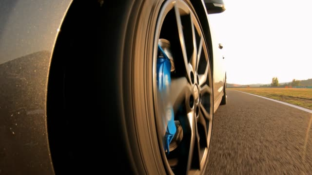 Car wheel spinning, driving on an empty road