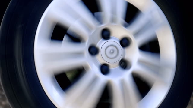 A car wheel with a shiny silver rim ride, turns to the right, to the left