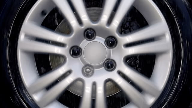 A car wheel with a shiny silver rim rides and strong shaking on bad road