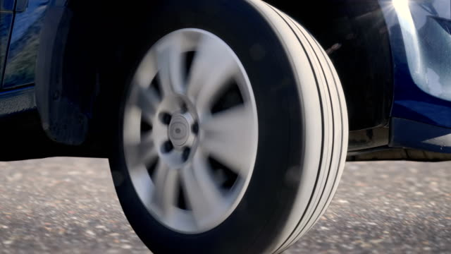 A car wheel with a shiny silver rim rides, turns to the right, to the left