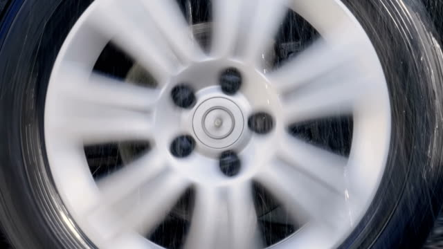 Car wheel with shiny silver rim rides in the rain drops and strong shaking