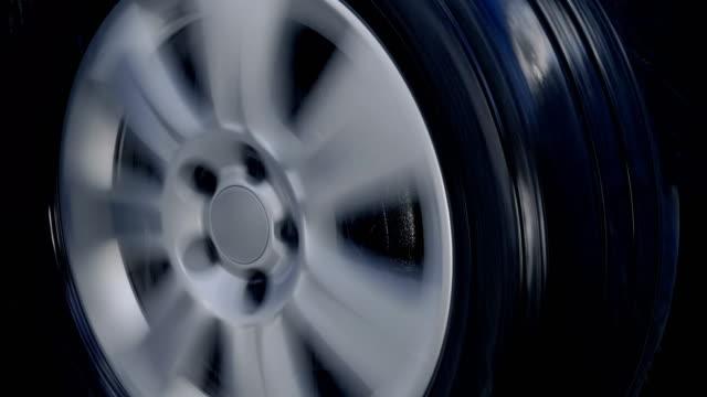 Car wheel with shiny silver rim rides in the rain drops