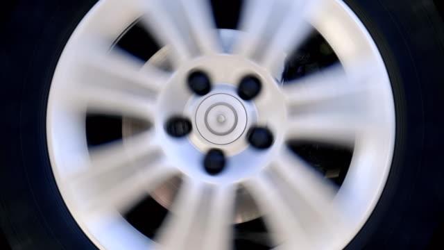 Car wheel with shiny silver rim rotates