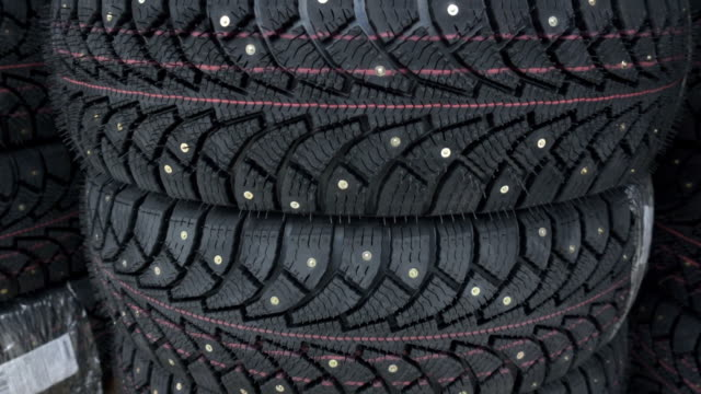 Car winter tires with spikes. Studded tires close up.