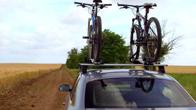 Car with bicycles on bike roof carrier on country road video