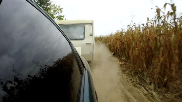 stockvideo's en b-roll-footage met auto met caravan, trailer gaan op onverharde landelijke weg. - caravan