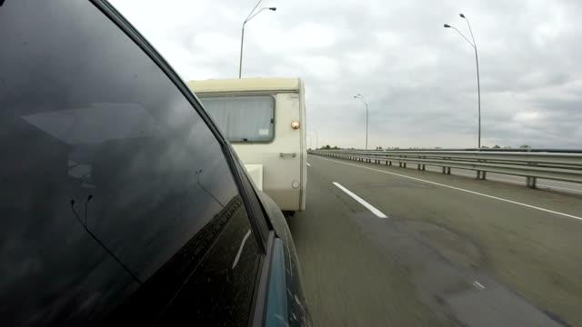 stockvideo's en b-roll-footage met auto met caravan, aanhangwagen gaat op weg, asfaltweg - caravan