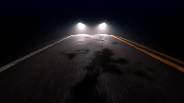 stockvideo's en b-roll-footage met auto met koplampen op volgt camera tracking langs country night road - mist donker auto