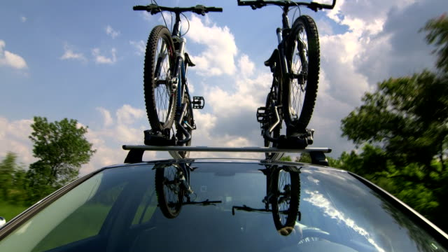 Car with two bicycles on bike roof carrier driving video