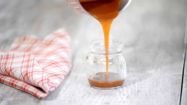 Caramel sauce pouring in a jar. Caramel sauce pouring in a jar. jar stock videos & royalty-free footage