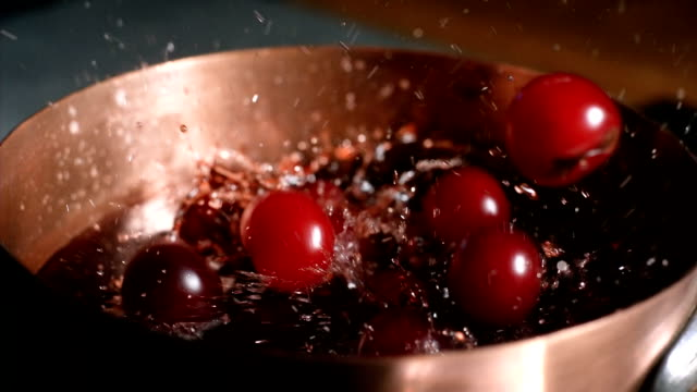 Caramelized cherries. Throwing and mixing cherries with caramel video