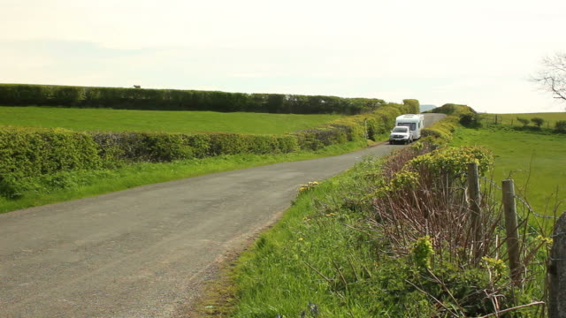 Caravan trailer travelling being towed through the countryside video