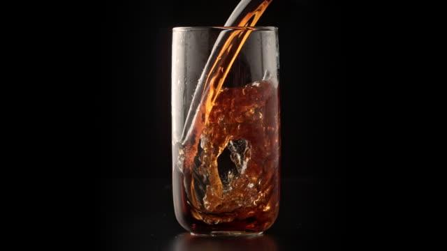 vídeos y material grabado en eventos de stock de bebida de cola carbonatada vertiendo en el vaso - cola gaseosa
